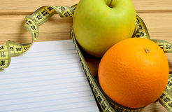 Notebook with apple and orange fruit Royalty Free Stock Photography
