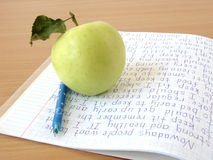 Notebook, Apple and Pen. Child's notebook with written story, a green apple and a pen on a wooden desk Royalty Free Stock Photography