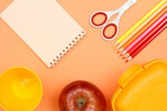 Notebook, apple, scissors, color pencils, plastic cup and lunch box. School supplies. School supplies. Notebook, apple, scissors, color pencils, plastic cup and stock images