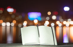 Notebook on the background of the city at night Royalty Free Stock Images
