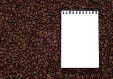 Notebook on the background coffee beans Royalty Free Stock Image
