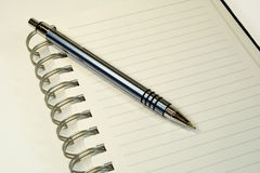 Notebook and ball pen. Notebook and the ball pen on the white background Stock Photo