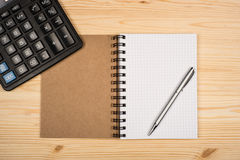 Notebook, ballpen and calculator. On wooden desk Royalty Free Stock Photos