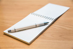 A notebook and ballpoint pen lying on a wooden table Stock Photography