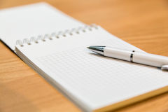 A notebook and ballpoint pen lying on a wooden table Royalty Free Stock Image