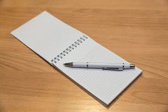A notebook and ballpoint pen lying on a wooden table Stock Image