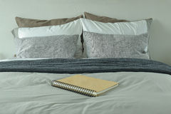 Notebook on bed with gray color scheme bedding Stock Photo