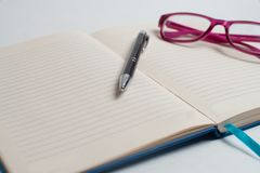 Notebook with black pen, Colorful notepads on the desk, Glasses on the desk with pen and cup of coffee, Computer keyboard with col. Notebook with black pen royalty free stock image