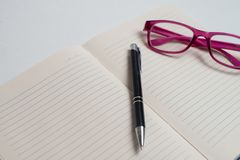 Notebook with black pen, Colorful notepads on the desk, Glasses on the desk with pen and cup of coffee, Computer keyboard with col. Notebook with black pen royalty free stock images