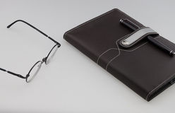 Notebook with black pen and glasses Royalty Free Stock Images