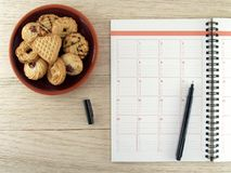 Notebook with black pen and pile of biscuit cookies in brown ceramics plate on wooden table floor royalty free stock photos