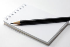 Notebook and a black pencil Royalty Free Stock Images