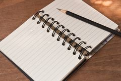 Notebook with black pencil, on wooden table.  Stock Photos