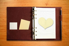 Notebook with blank heart shape paper Stock Photo