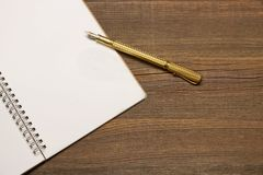 Notebook With Blank Page  And Golden Pen  On Wood Table Royalty Free Stock Photo