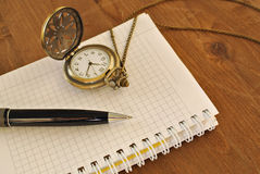 Notebook with blank pages, black pen and vintage pocket watch on wooden background Stock Photos