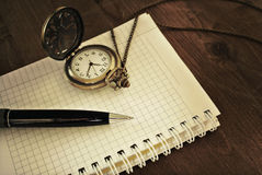 Notebook with blank pages, black pen and vintage pocket watch on wooden background Royalty Free Stock Photography