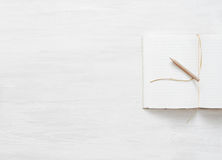 Notebook with blank pages and a pencil on a white wooden surface Royalty Free Stock Photo