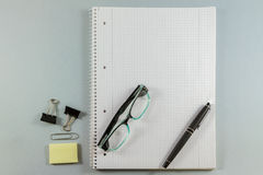 Notebook with blank paper, color sticky notes, pen, glasses and Stock Photos