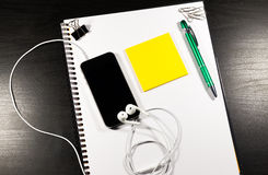 Notebook with blank paper, color sticky notes, pen, smartphone and clips on a wooden table Royalty Free Stock Image