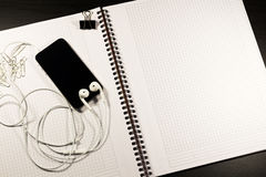 Notebook with blank paper, smartphone and clips on a wooden table Stock Photo