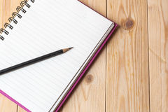Notebook. Blank notebook and pencil on wooden background Royalty Free Stock Image