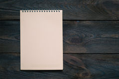 Notebook with blank sheet on a wooden surface Stock Images
