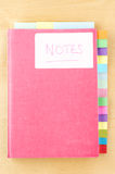 Notebook with Blank Tab Dividers. Pink notebook on a light wood background. White 'Notes' label on cover, three tab dividers sectioning book along top edge and stock images