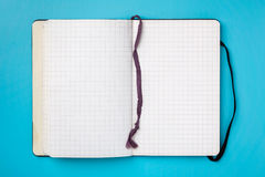 Notebook on blue background. Stock Photography