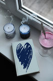 Notebook with blue design heart cover on windowsill. Blow out the candles with smoke, smoothie in tall glass goblet Stock Photography