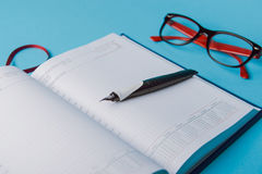 Notebook on blue paper. open diary and pen to record Stock Images