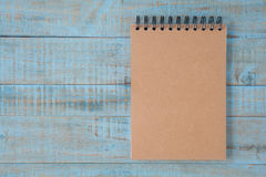 Notebook on blue wood table Stock Photography