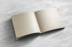 Notebook or book. Blank notebook or book of kraft paper on light wooden background. Responsive design mockup stock images