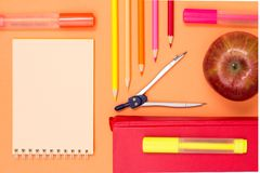 Notebook, book, compass, color pencils and apple on pink background. Top view. Back to school concept. School supplies stock photo
