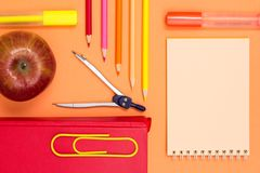 Notebook, book, compass, color pencils and apple on pink background. Top view. Back to school concept. School supplies royalty free stock photo