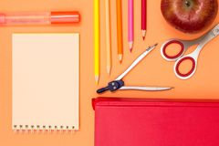 Notebook, book, compass, color pencils and apple on pink background. Top view. Back to school concept. School supplies stock photography