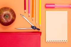 Notebook, book, compass, color pencils and apple on pink background. Top view with copy space. Back to school concept. School supplies. Pastel colors stock image