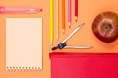 Notebook, book, compass, color pencils and apple on pink background. Top view with copy space. Back to school concept. School supplies. Pastel colors stock images