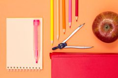 Notebook, book, compass, color pencils and apple on pink background. Top view with copy space. Back to school concept. School supplies. Pastel colors royalty free stock photography