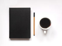 Notebook or book with pen and hot black coffee on white desk. top view. flat lay. Royalty Free Stock Images