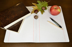 Notebook, books and pencils. Opened notebook with pencil, pen, chestnuts, dry leaf and books on wooden desk - fall composition Royalty Free Stock Photo
