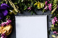 Notebook and bouquet of bright flowers for Women day, Mother day background. Flat lay.Top view royalty free stock images