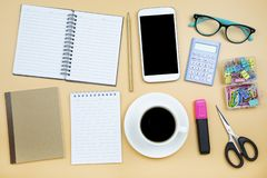 Notebook brown cover mobile phone calculator and black coffee wh. Ite cup green glasses on orange background pastel style with copyspace flatlay stock photo