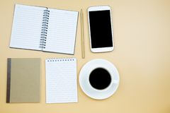 Notebook brown cover mobile phone calculator and black coffee wh. Ite cup green clock on orange background pastel style with copyspace flatlay stock photography
