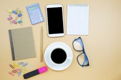 Notebook brown cover mobile phone calculator and black coffee wh. Ite cup blue glasses on orange background pastel style with copyspace flatlay stock images
