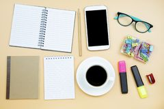 Notebook brown cover mobile phone calculator and black coffee wh. Ite cup green glasses on orange background pastel style with copyspace flatlay royalty free stock image