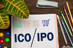 Notebook with a Business notes ICO initial coin offering vs IPO Initial Public Offering on the office table with tools. Concept IPO and ICO with elements of Royalty Free Stock Images
