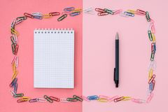 Notebook in a cage. Colored paper clips in the form of a frame and notebook on spirals in a cage with pen on a pink-coral background. Concept back to school stock image