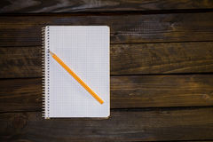 Notebook in a cage and yellow pencil. On a wooden background Stock Photo