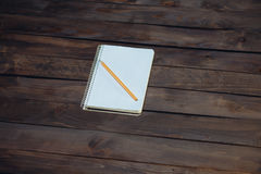 Notebook in a cage and yellow pencil Royalty Free Stock Photos